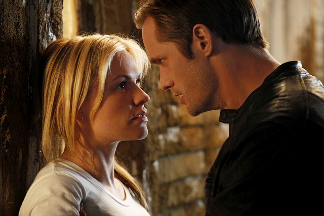 Screenshot from True Blood. Sookie is wearing a white top and pressed against a wall by Eric who is wearing a black leather jacket.