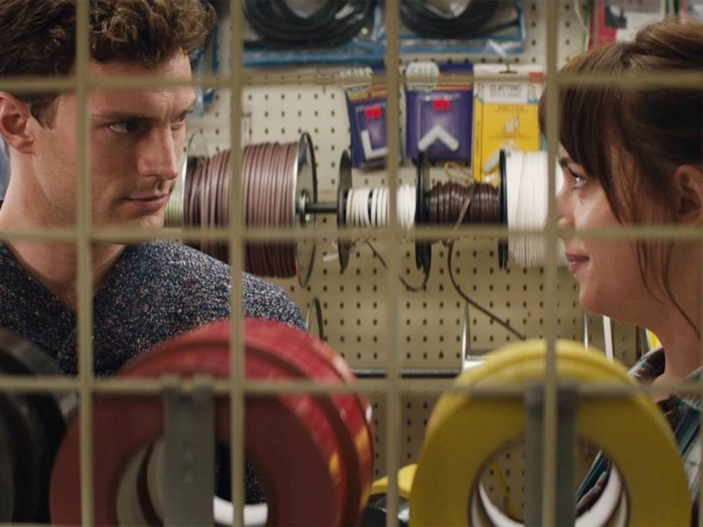 Jamie Dornan stars as Christian Grey and Dakota Johnson stars as Anastasia Steele in Focus Features' Fifty Shades of Grey (2015)