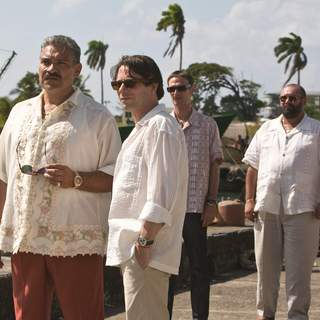 (L-R) General Modrano (JOAQUIN COSIO), Dominic Greene (MATHIEU AMALRIC), Elvis (ANATOLE TAUBMAN),  and Lt. Orso (JESUS OCHOA) meet on the Haitian Quayside. Location: Colon, Panama. Photo by: Karen Ballard.