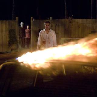 The Man in the Mask (KIP WEEKS) and Pin-Up Girl (LAURA MARGOLIS) stalk James Hoyt (SCOTT SPEEDMAN) in Rogue Pictures' The Strangers (2008). - the_strangers06