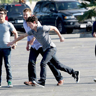Jonas Brothers playing American football between scenes on the set 'Chasing Butterflies'