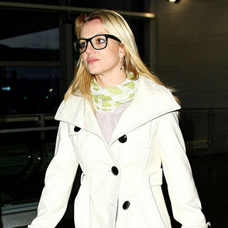 Britney Spears - Britney Spears wearing large black rimmed glasses and a white coat catches a flight