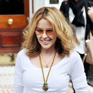 Kylie Minogue leaving her home wearing mustard coloured trousers