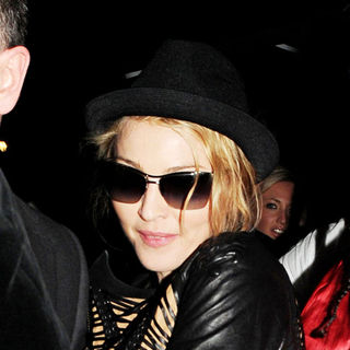 Madonna is escorted out of Aura night club by her personal bodyguard just after 1AM